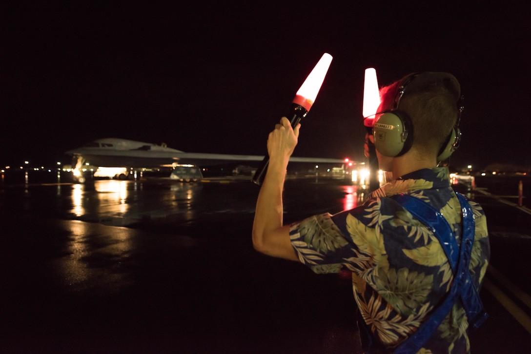 Senior Airman Hayden Thayer, 509th Maintenance Group crew chief deployed from Whiteman Air Force Base, Missouri, marshals a B-2 Spirit at Joint Base Pearl Harbor-Hickam, Hawaii Jan. 31, 2018
