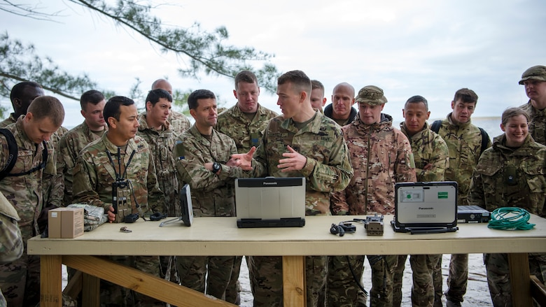 Service members from the Joint Communications Support Element and the British Army's 30th Signal Regiment gather around U.S. Army Staff Sgt. Kevin Shells (center), a JCSE systems team chief, at Beer Can Island, Fla. Jan. 30, 2019, as he demonstrates how to set up and utilize communications equipment in a deployed environment with no power source. As part of the Cobb Ring exercise, the two nations trained together to demonstrate capabilities with coalition partners and strengthen relationships.