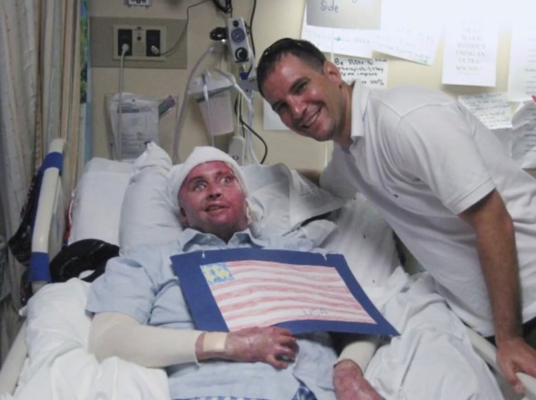 Air Force Lt. Col. Kevin Lombardo, 341st Missile Security Forces Squadron commander, right, visits with Army Spc. Joel Tavera in the hospital.