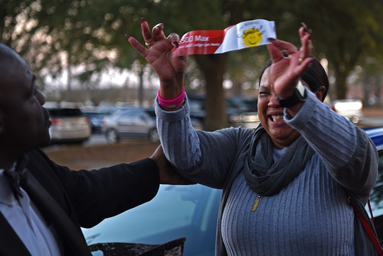 Derrick Rhems, 20th Force Support Squadron marketing and promotions director, left, congratulates a Team Shaw member on her alternate prize during a Smile Campaign car giveaway wrap-up party at Shaw Air Force Base, S.C., Jan. 31, 2019.