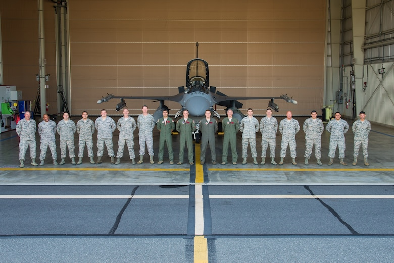 A picture of members of the 177th Fighter Wing's Aerospace Control Alert mission posing for a group photo in front of a U.S. Air Force F-16C Fighting Falcon.