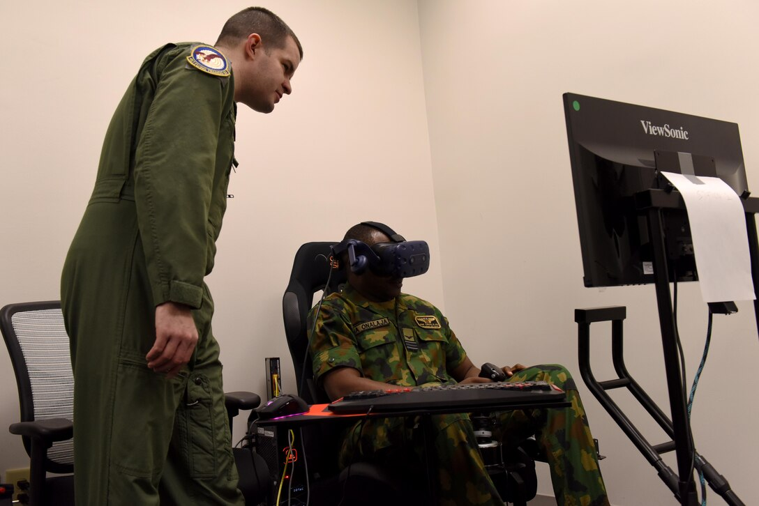 Maj. James Stillwagon, 37th Flying Training Squadron instructor pilot, shows Squadron Leader Adedamola Onalaja, Nigerian Air Force, how their virtual reality training works Jan. 23, 2019, on Columbus Air Force Base, Mississippi. The Nigerian Air Force members visited Columbus AFB to check on one of their students and to see the different aspects of pilot training. (U.S. Air Force photo by Senior Airman Beaux Hebert)