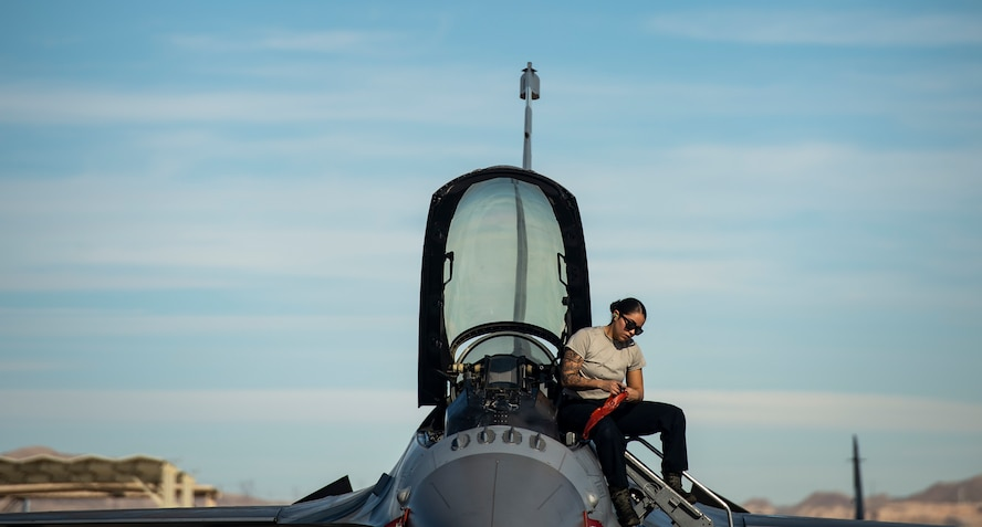 An Airman sits on the edge of an F-16 Fighting Falcon fighter jet.