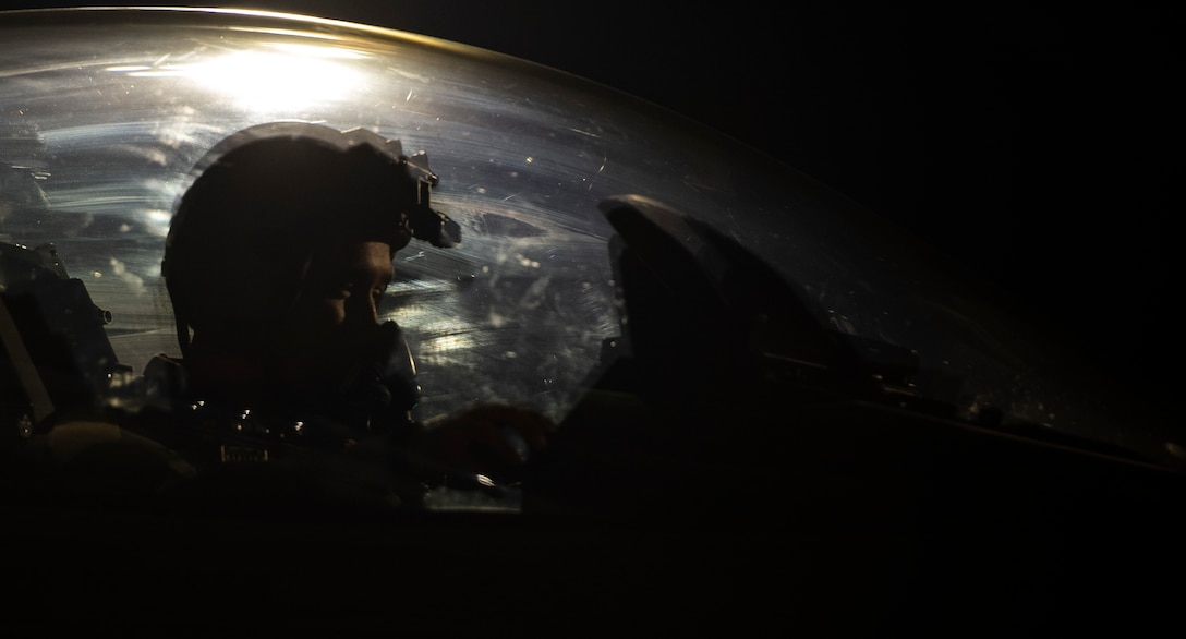 A pilot sits in the cockpit of an F-16 fighting Falcon fighter jet at night.