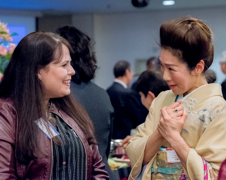 Carrie Waller, wife of Lt. Col. Brian Waller, 515th Air Mobility Operations Group deputy commander, talks to a member of Hamura-Yokota Friendship Club during the U.S.- Japan Joint New Year's Party at Yokota Air Base, Japan, Jan. 26, 2019.