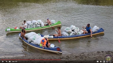 A group of people paddle canoes in a river. The canoes are filled with bags of trash.