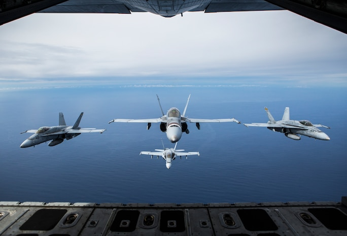 """Four F/A-18C Hornets assigned to Marine Fighter Attack Squadron 323 fly in formation behind a KC-130J Super Hercules attached to Marine Aerial Refueler Transport Squadron 352, Marine Aircraft Group 11, during a readiness exercise called the 'Elephant Walk' above Marine Corps Air Station Miramar, Calif., Feb. 1, 2019.  MAG-11 conducted this training to exercise its real-world capabilities. Exercises such as this provide realistic, relevant training necessary for 3rd MAW to """"Fix, Fly, and Fight"""" as the Marine Corps' largest aircraft wing and ensures the unit remains combat-ready, inter-operable, deployable on short notice, and lethal when called into action."""