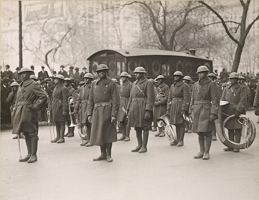"""Soldiers of the 369th Infantry Regiment band stand at rest as they wait to march up Fifth Avenue in New York City on Feb. 17, 1919, during a parade held to welcome the New York National Guard unit home. More than 2,000 Soldiers took part in the parade up Fifth Avenue. The Soldiers marched seven miles from downtown Manhattan to Harlem. The band was led by noted musician Lt. James Reese """" Jimmie"""" Europe, seen at center wearing glasses."""