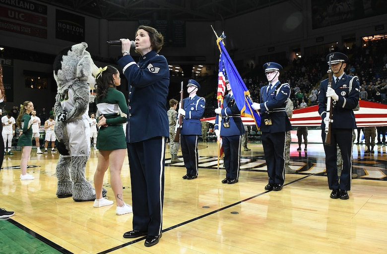 Staff Sgt. Joanne Griffin, U.S. Air Force Band of Flight vocalist, sings the national anthem as members of the Wright-Patterson Air Force Base Honor Guard present the colors at a military appreciation basketball game.