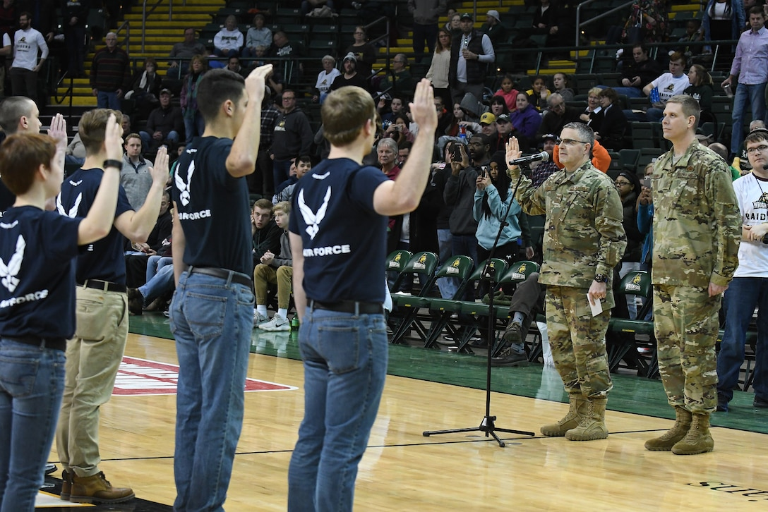 Maj. Gen. William Cooley, Air Force Research Laboratory commander, administers the oath of enlistment to 25 future Airmen at a Wright State University basketball game Jan. 26, 2018 athe the Erwin J. Nutter Center. (Courtesy photo).