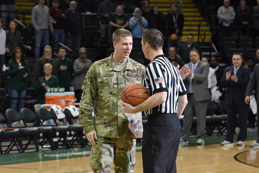 Chief Master Sgt. Kennon Arnold, Air Force Research Laboratory command chief, delivers the official game ball to the official at half court prior to the Wright State University men's basketball game on Jan. 26, 2018. (Courtesy photo).