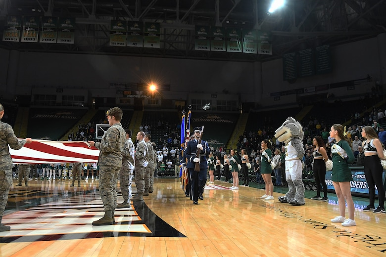 Members of the Wright-Patterson Air Force Base honor guard prepare to present the colors for the national anthem while 22 Airmen from the United States Air Force School of Aerospace Medicine present a large American flag at a Wright State men's basketball game on Jan. 26, 2018, in the Erwin J. Nutter Center. (Courtesy photo).