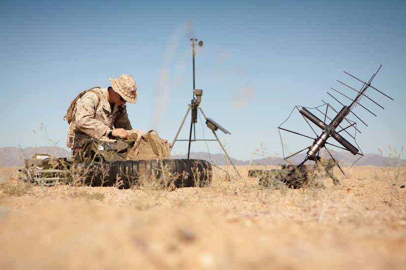 A Marine reprograms a portable radio.