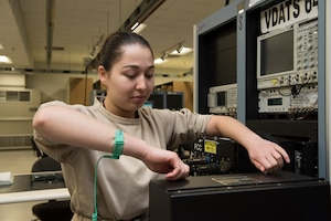 Airman 1st Class Vera Schwenk, an avionics technician assigned to the 509th Maintenance Squadron, removes a panel from a part of the Versatile Diagnostics Automatic Test Station.