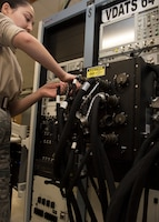 Airman 1st Class Vera Schwenk, an avionics technician assigned to the 509th Maintenance Squadron, adjusts electrical cables of the Versatile Diagnostics Automatic Test Station.