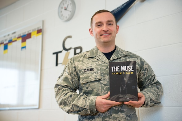 "Tech. Sgt. Charlie Daube, a munitions inspector for the 167th Maintenance Squadron, holds a copy of his recently published novel, ""The Muse."" (U.S. Air National Guard photo by Senior Airman Teddy Michon)"