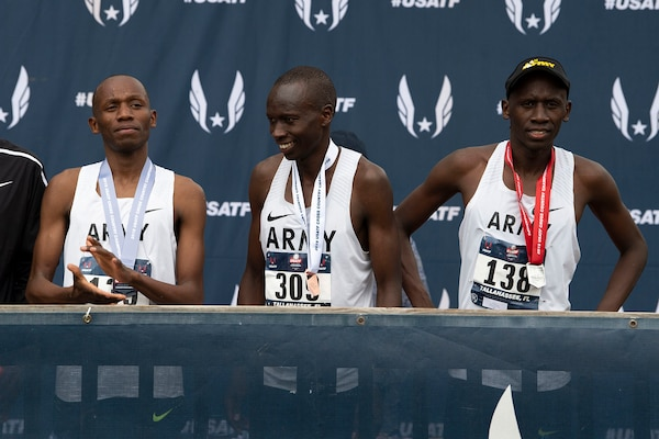 From left, Army Sgt. Hillary Bor, Army Sgt. Leonard Korir, and Army Sgt. Emmanuel Bor stand on an awards stage with their medals after placing the 2nd, 3rd, and 4th in the USA Track and Field Cross Country Championship