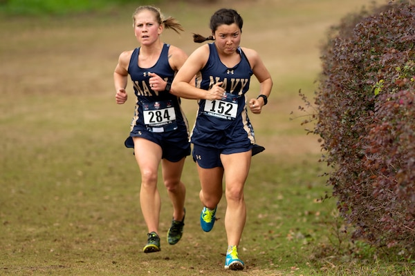 Two athletes wearing race numbers jog on flat terrain.