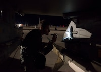 A pilot uses a flashlight to inspect the wing of an F-16 Fighting Falcon fighter jet.