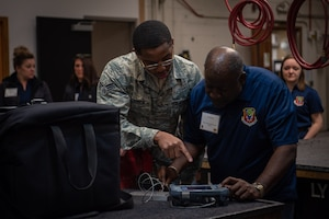 Senior Airman Armond Conner, 56th Equipment Maintenance Squadron nondestructive inspection journeyman, teaches C.D. Houston, Mountain Home Military Affairs Committee board member, how to detect cracks in a metal plate, Jan. 31, 2019 at Luke Air Force Base, Ariz.