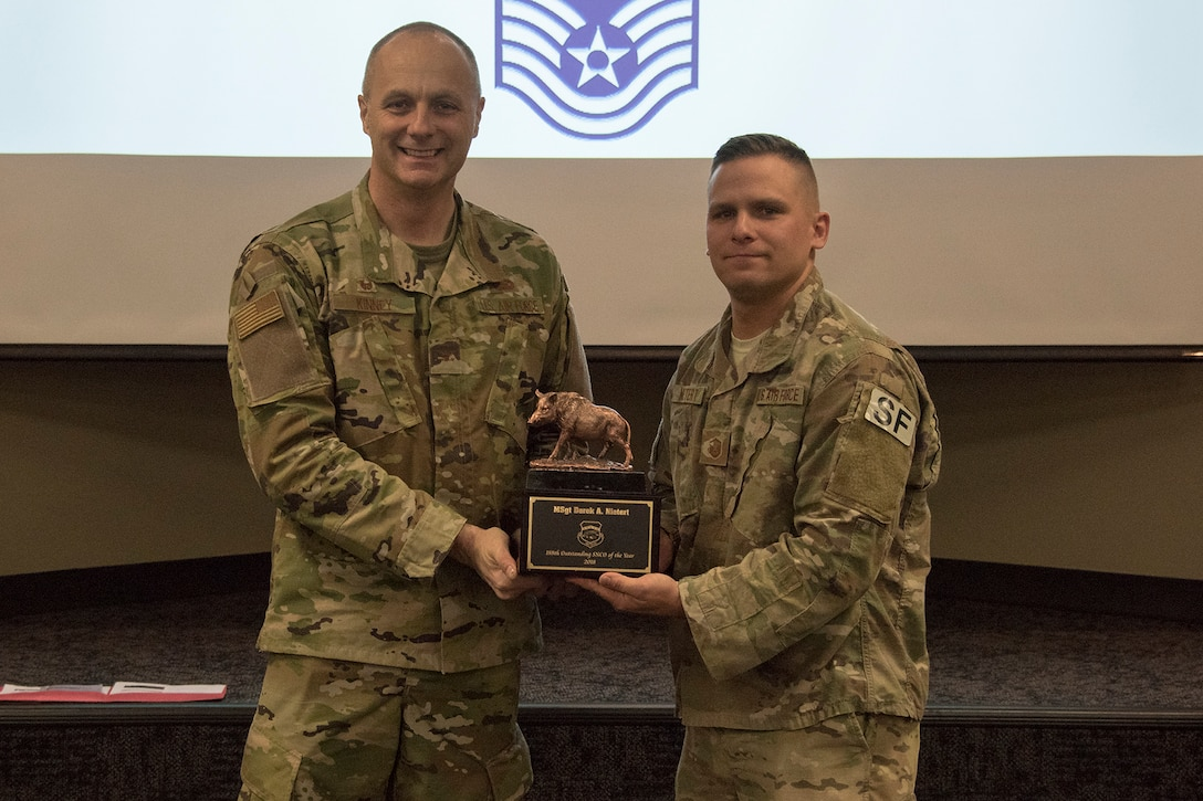 Col. Robert I. Kinney, 188th Wing commander, presents Master Sgt. Derek A. Nietert, the 188th Wing Outstanding Senior NCO of the Year, with a trophy at a commander's call held at Ebbing Air National Guard Base, Ark., Jan. 13, 2019. (U.S. Air National Guard photo by Tech. Sgt. John E. Hillier)
