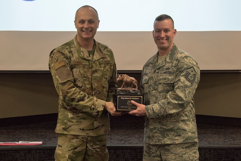 Col. Robert I. Kinney, 188th Wing commander, presents Master Sgt. Robert M. Stephens, the 188th Wing Outstanding First Sergeant of the Year, with a trophy at a commander's call held at Ebbing Air National Guard Base, Ark., Jan. 13, 2019. (U.S. Air National Guard photo by Tech. Sgt. John E. Hillier)