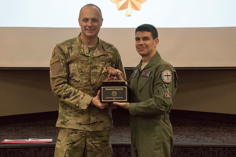 Col. Robert I Kinney, 188th Wing commander, presents Maj. James B. Stewart IV, the 188th Wing Outstanding Field Grade Officer of the Year, with a trophy at a commander's call held at Ebbing Air National Guard Base, Ark., Jan. 13, 2019. (U.S. Air National Guard photo by Tech. Sgt. John E. Hillier)