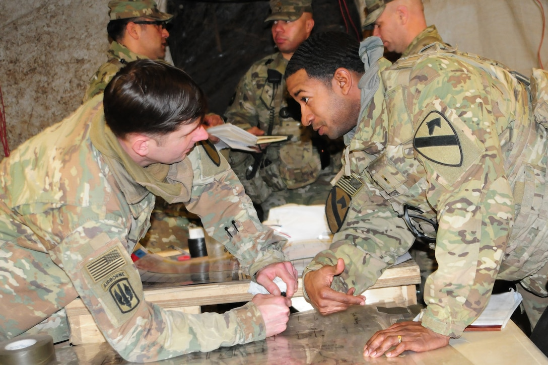 Two soldiers confer over a map