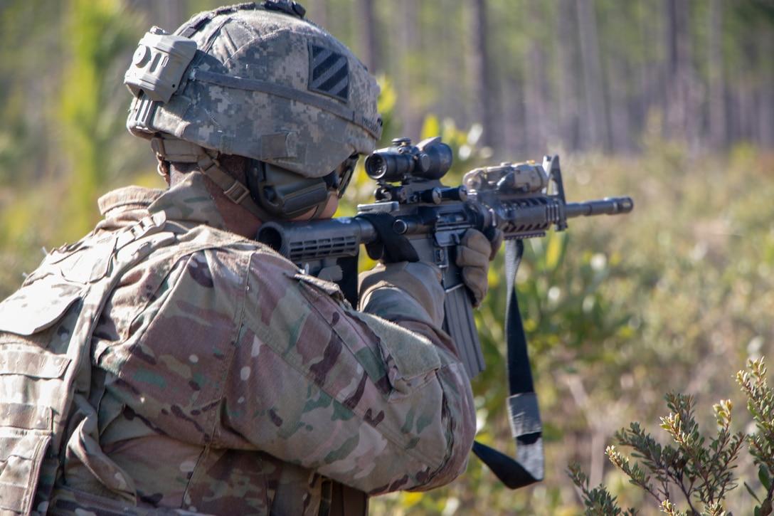 A soldier aims a rifle.