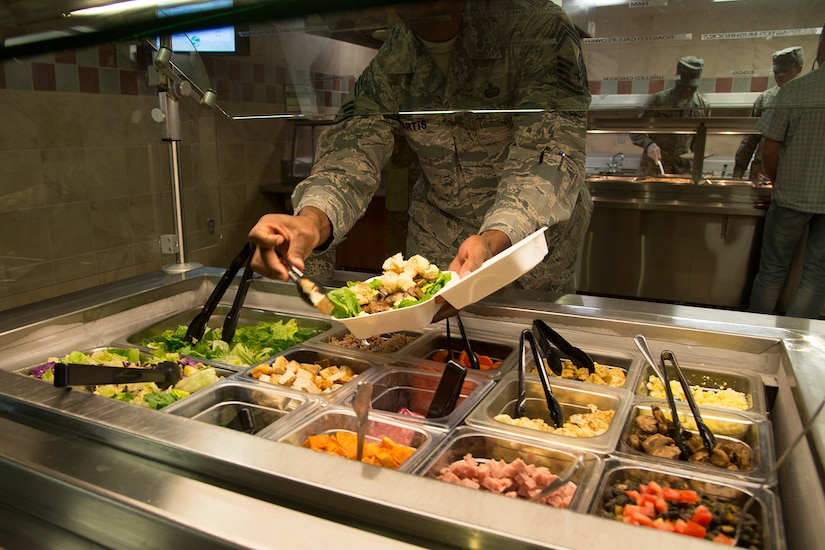 A service member uses a salad bar.