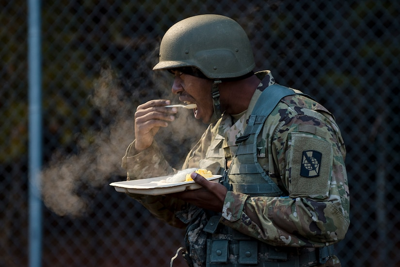 A soldier eats outdoors in the cold.