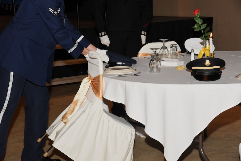 A Joint Service Color Guard member sets an Air Force cover on an empty table reserved to honor missing comrades in arms at the Annual Awards Ceremony at the McNeese Convention Center, San Angelo, Texas, Feb. 1, 2019. The table was set for five, one seat from each branch of service, symbolizing their inability to share the evening's festivities.  (U.S. Air Force photo by Airman 1st Class Abbey Rieves/ Released)