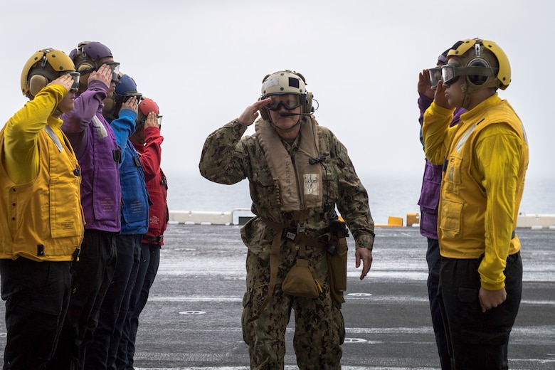 EAST CHINA SEA (Feb. 5, 2019) Commander of U.S. 7th Fleet, Vice Adm. Phil Sawyer, renders a salute through side boys on the flight deck of the amphibious assault ship USS Wasp (LHD 1) during a visit between U.S. and Japan military officials to observe amphibious operations at sea. Wasp, flagship of the Wasp Amphibious Ready Group, with embarked 31st Marine Expeditionary Unit, is operating in the Indo-Pacific region to enhance interoperability with partners and serve as a ready-response force for any type of contingency.