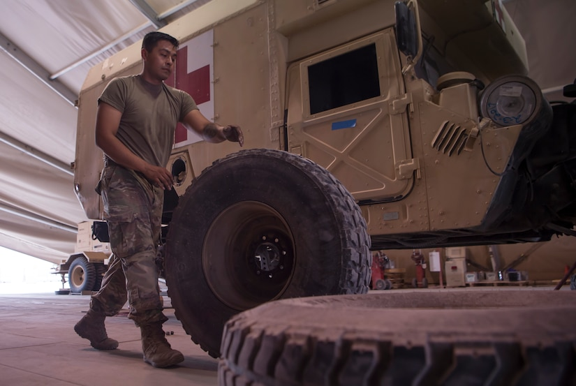 U.S. Army Spc. Abraham Garcia, Echo Company, 1st Battalion, 43rd Air Defense Artillery (ADA) Battalion, 11th ADA Brigade wheeled vehicle mechanic, moves a military vehicle wheel as part of a routine tire rotation Jan. 28, 2019, at Al Udeid Air Base, Qatar. Soldiers of Echo Company perform mechanical work and repairs for various equipment and assets that support Al Udeid's air defense capabilities, including surface-to-air missile systems. (U.S. Air Force photo by Tech. Sgt. Christopher Hubenthal)