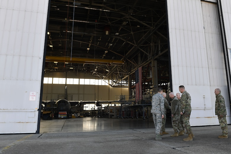 Men walk into a hangar.