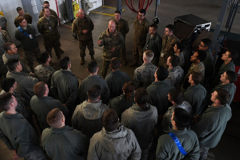 Airmen stand around a man.