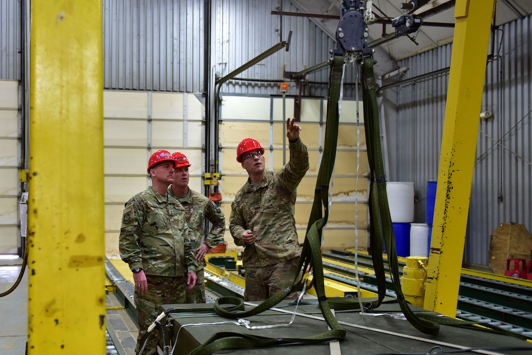 Men stand in front of a hoist and ropes.