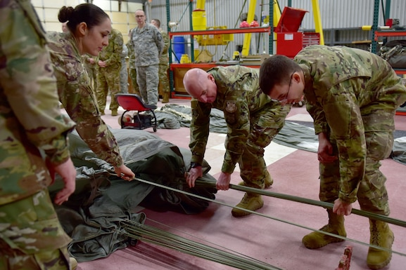 Men and women in military camouflage uniform pull ropes on a parachute.