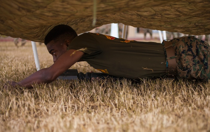 Cpl. Shaconey White, sourcing cell noncommissioned officer in charge with Marine Forces Reserve G-1 Operations, low crawls under a platform during the MARFORRES Log Race Competition at Marine Corps Support Facility New Orleans, Jan. 17, 2019