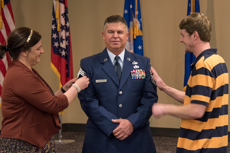 Chief Master Sgt. Nathan E. Harrell, 288th Operations Support Squadron superintendent, has his stripes pinned on by family members during his promotion ceremony at Ebbing Air National Guard Base, Fort Smith, Ark., Feb. 2, 2019. Harrell has over 36 years of military service, and has been a member of the 188th Wing since 1985. (U.S. Air National Guard photo by Staff Sgt. Emmanuel Gutierrez)