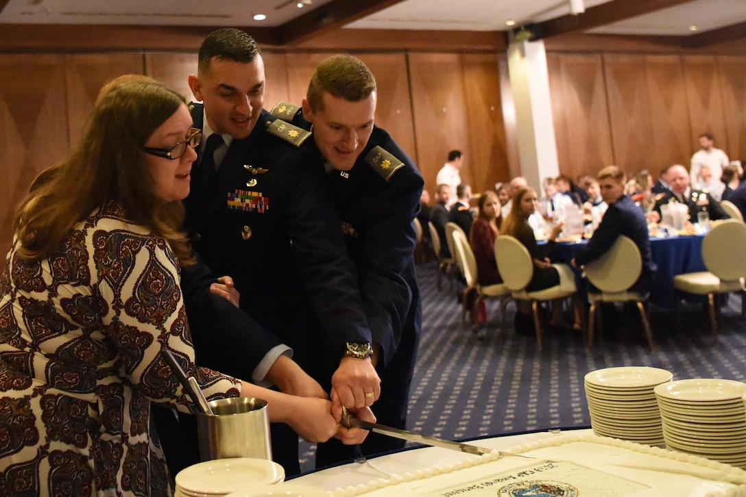 Distinguished guests cut a cake with a ceremonial sword at a Civil Air Patrol banquet at the Officer's Club on Ramstein Air Base, Germany, Feb. 2, 2019. CAP provides a unique opportunity for youth to experience life in military, teaching discipline and leadership to the next generation of possible Airmen. (U.S. Air Force photo by Airman 1st Class Milton Hamilton)