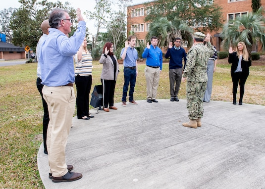 Naval Surface Warfare Center Panama City Division Commanding Officer Capt. Aaron Peters administers the oath of office to 10 newly hired federal civil service employees at the flagpole Feb. 4, 2019. U.S. Navy photos by Eddie Green