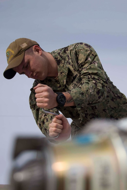 U.S. Navy Petty Officer Dylan Scott, a mineman with Navy Munitions Command Atlantic Unit Charleston makes final adjustments to an inert naval mine at Barksdale Air Force Base, Louisiana, Jan. 30, 2019.   The mines will be laid by a B-52 Stratofortress operating out of Barksdale AFB.  (U.S. Air Force photo by Master Sgt. Ted Daigle)