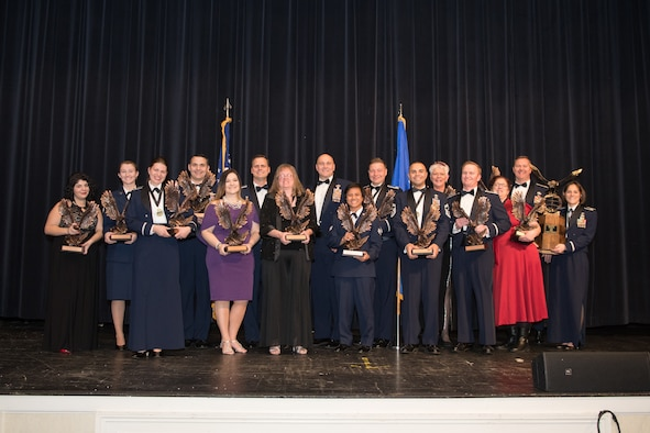 Annual award winners pose with 436th Airlift Wing commander Col. Joel Safranek and command chief Chief Master Sgt. Anthony Green at the conclusion of the 2018 Annual Awards Ceremony Feb. 1, 2019, at the Rollins Center in Dover Downs Hotel and Casino, Dover, Delaware. 13 individuals and one team were recognized as the best in the wing and received the coveted eagle trophies for their respective categories. (U.S. Air Force photo by Mauricio Campino)