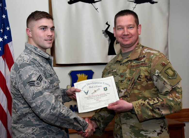 Senior Airman William Merth, 22nd Aircraft Maintenance Squadron integrated flight control system apprentice, left, is recognized by Col. Mark Baran, 22nd Air Refueling Wing vice commander, for earning a score of 95 percent on his Career Development Course Feb. 5, 2019, at McConnell Air Force Base, Kan. CDCs help enlisted personnel complete the specialty knowledge portion of on-the-job training for their specific career fields.