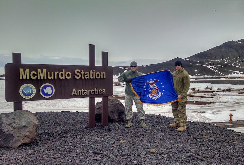 Chief Master Sgt. Troy Erlandson, 114th Fighter Wing occupational safety manager, holds the South Dakota Air National Guard flag with another Airman during his trip to McMurdo Station, Antarctica, where he worked directly for Joint Force Antarctica to support their research mission.