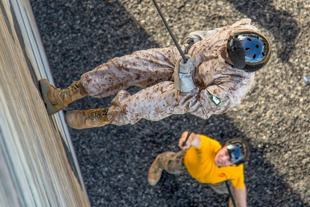 A Marine rappels down a wall while a trainer waits at the bottom.