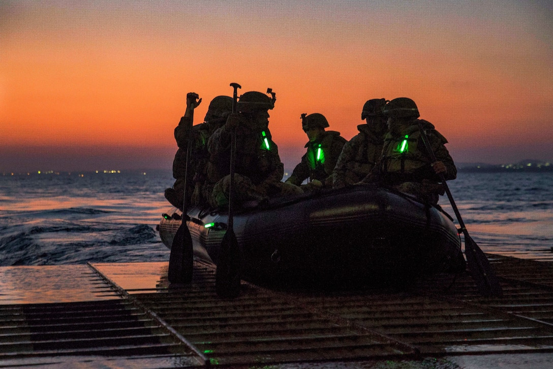 Marines sit in a rubber boat about to head out to sea.
