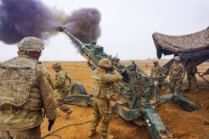 Soldiers fire a howitzer.