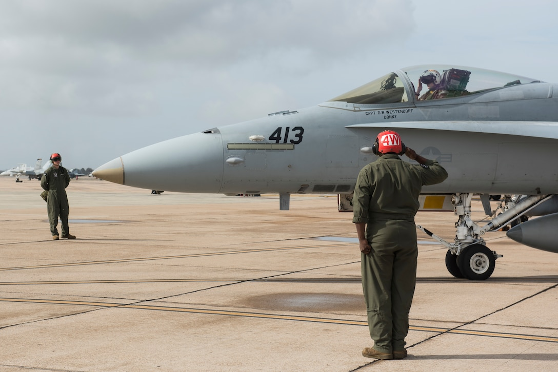 U.S. Marine Corps Sgt. Ben Liberal, 323d Marine Fighter Attack Squadron ordinance team leader, salutes an F/A-18C Hornet pilot prior to takeoff during joint exercise Winter Fury at Marine Air Station Miramar, San Diego, Calif., Jan. 18, 2019. Winter Fury involved both Marine F/A-18C Hornets, and Navy F-35C Lightning II's, partnering with Air Force F-22 Raptors to perform air-to-air combat, while protecting ground assets.